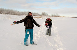 Two students walking through snow in an open field