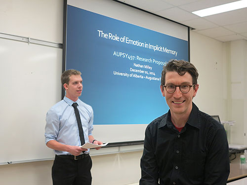 Associate Professor Sean Moore posing in front of a student presentation